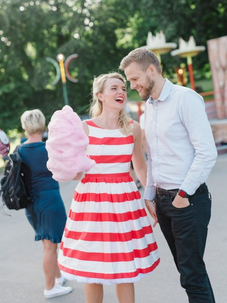 50s Retro Engagement Love Shoot of girl in red and white stripy dress being kissed on the cheek by her Fiancé while she holds pink candy floss at Bakken Copenhagen Denmark