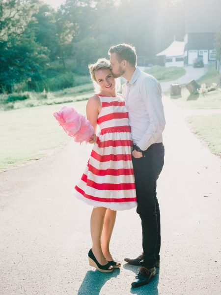 50s Retro Engagement Love Shoot of girl in red and white stripy dress holding candy floss as her Fiancé kisses her in the cheek Bakken Copenhagen Denmark