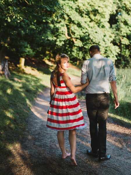 50s Retro Engagement Love Shoot of girl in red and white stripy dress walking with Fiance away from camera. Girl looking back at camera. I a wood at Bakken Copenhagen Denmark