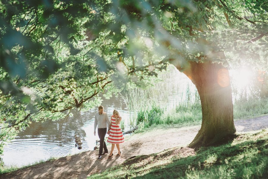 50s Retro Engagement Love Shoot of girl in red and white stripy dress walking with Fiance under large tress with beautiful light streaming through Bakken Copenhagen Denmark