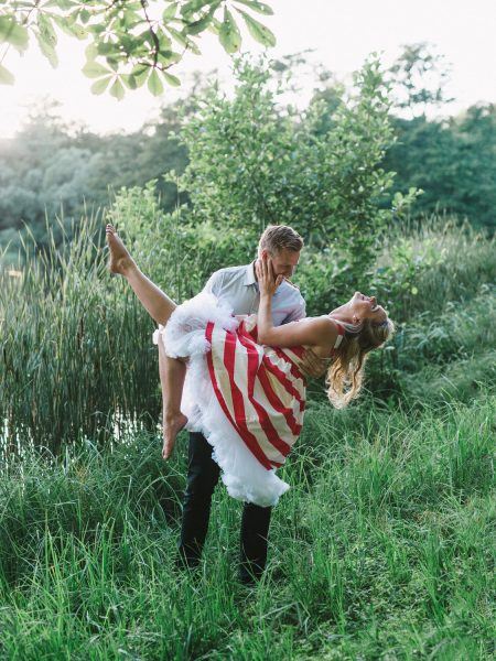 50s Retro Engagement Love Shoot of girl in red and white stripy dress being playful led dipped bygenFiance at the edge of a lake Bakken Copenha Denmark