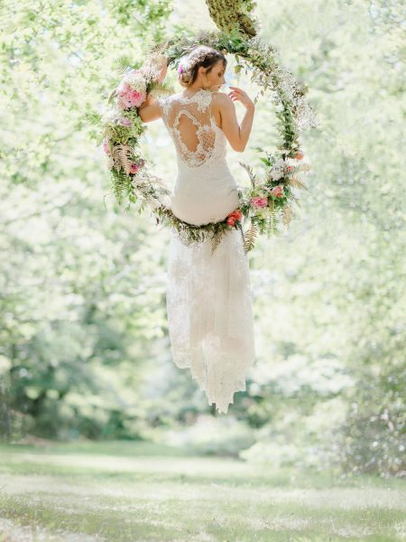 Dreamy Fine Art image of the back view of the Bride sitting in a floral hoop in a forest wearing a Tara Bradley Birt dress that is cascading down