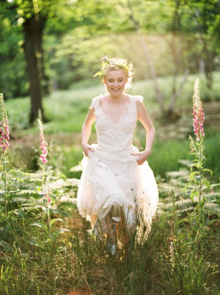 Fine Art fuji400h film full length image of a Bride wearing luxe boho beaded wedding dress and rustic floral crown running happily through a magical forest with fox gloves and evening light for Tara Bradley-Birt bridal fashion shoot