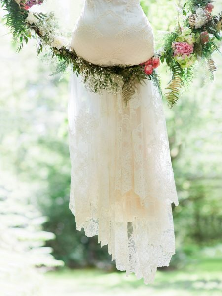 Detail shot of the bottom section of a Bride's boho lace dress as she sits in a suspended floral and foliage hoop in a forest for Tara Bradley-Birt bridal fashion shoot