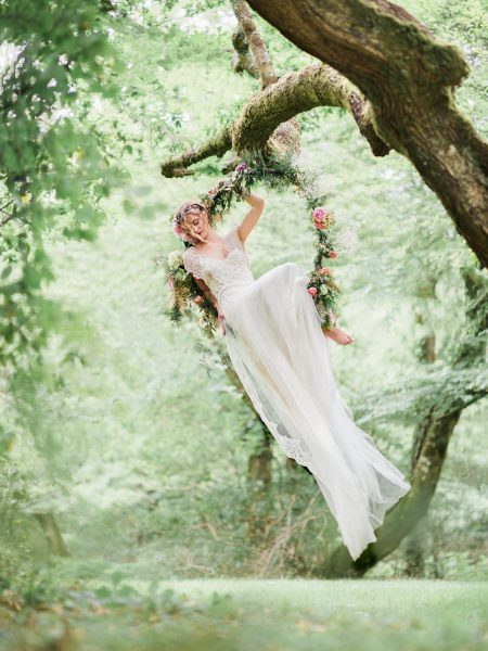 Dreamy Fine Art image of a Bride sitting in a floral hoop in a forest scene wearing a Tara Bradley Birt dress that is cascading down