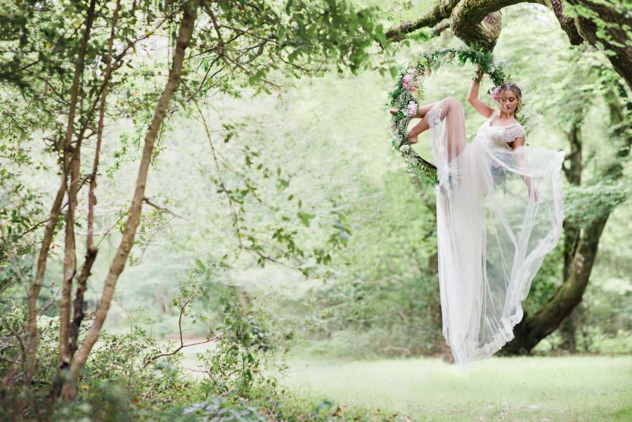 Dreamy Fine Art image of a Bride sitting in a floral hoop holding dress out in a forest scene wearing a Tara Bradley-Birt dress that is cascading down
