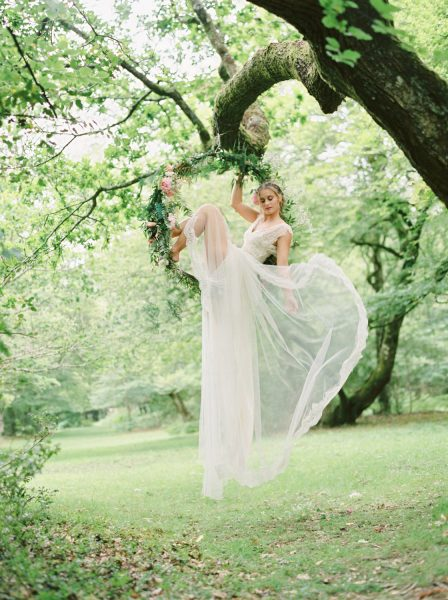 Dreamy Fine Art Fuji 400h image of a Bride sitting in a floral hoop holding dress out in a forest scene wearing a Tara Bradley-Birt dress that is cascading down