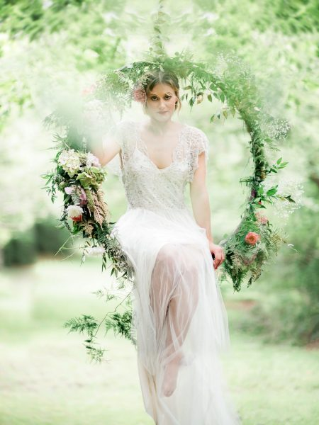 Bride wearing wedding dress sitting head on in a floral foliage covered aerial hoop in a magical forest for Tara Bradley-Birt bridal fashion shoot