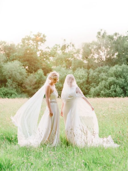 Fine Art fuji400h film full length portrait of two Brides wearing wedding dresses with billowing veils blowing in a dreamy bathed in golden light field for Tara Bradley-Birt bridal fashion shoot