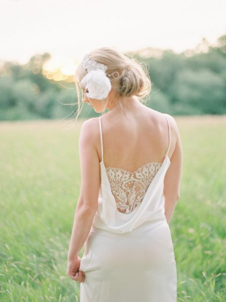 Fine Art fuji400h film portrait of back of a Bride showing off intricate lace back detailing in a dreamy bathed in golden light field for Tara Bradley-Birt bridal fashion shoot