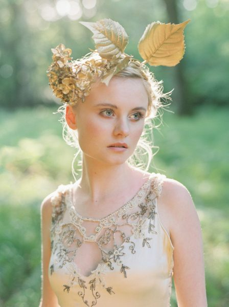 Fine Art fuji400h film portrait image of a Bride wearing a boho gold leaf headdress and gold embellished beaded wedding dress in a magical forest with evening light for Tara Bradley-Birt bridal fashion shoot