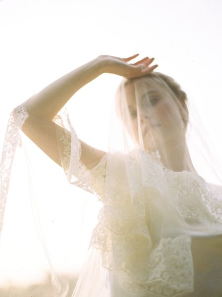 Fine Art fuji400h film portrait of Bride with arm raised up to forehead with dreamy light filtering through veil for Tara Bradley-Birt bridal fashion shoot