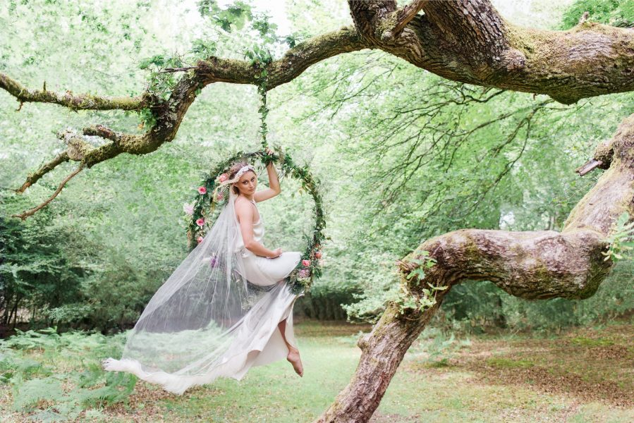 Dreamy Fine Art Fuji 400h image of a Bride sitting in a floral hoop in a forest scene wearing a Tara Bradley-Birt dress that is cascading behind her
