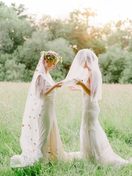 Fine Art fuji400h film full length portrait of two Brides inspecting each other's veils wearing wedding dresses in a dreamy bathed in golden light field for Tara Bradley-Birt bridal fashion shoot