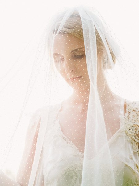 Fine Art fuji400h film portrait of Bride with dotty spotted veil looking down with dreamy light filtering through veil for Tara Bradley-Birt bridal fashion shoot