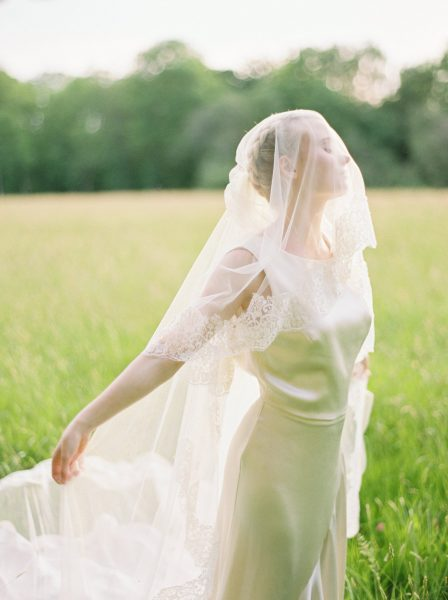 Fine Art fuji400h film portrait of Bride with arms extended behind herself in a dreamy moment with light filtering through veil for Tara Bradley-Birt bridal fashion shoot