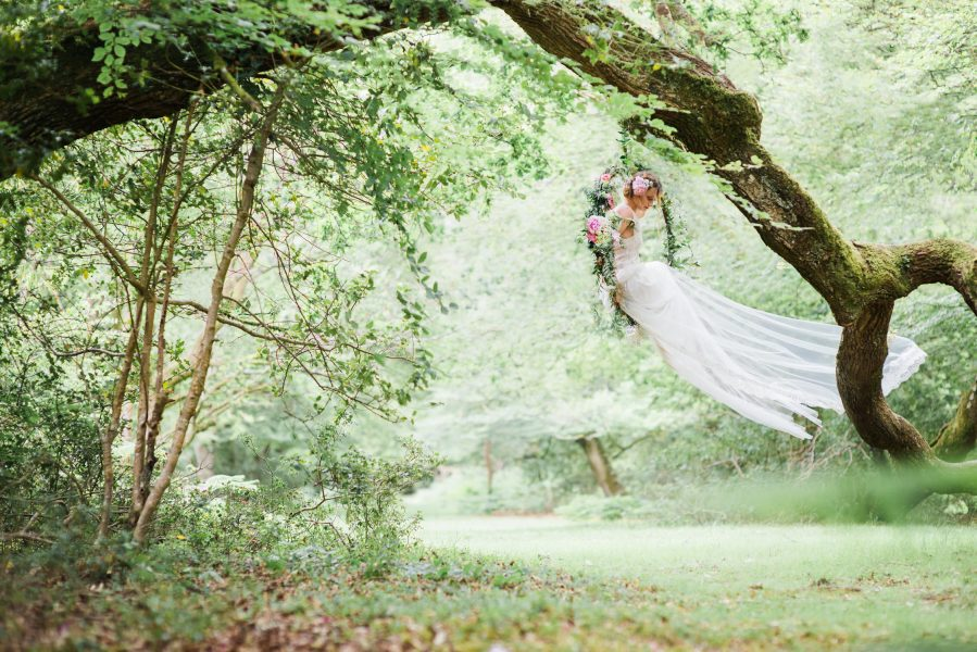 Dreamy Fine Art Fuji 400h image of a Bride sitting in a floral hoop in forest scene wearing a Tara Bradley-Birt dress that is cascading outwards blown by wind