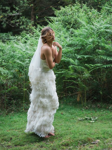 Dreamy Fine Art Fuji 400h image of a Bride walking in an ostrich feather wedding dress in a forest fern scene for Tara Bradley-Birt dress