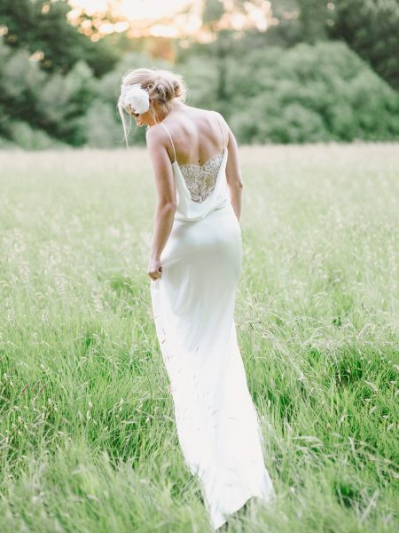 Full length Fine Art fuji400h film portrait of back of a Bride showing off intricate lace back detailing in a dreamy bathed in golden light field for Tara Bradley-Birt bridal fashion shoot