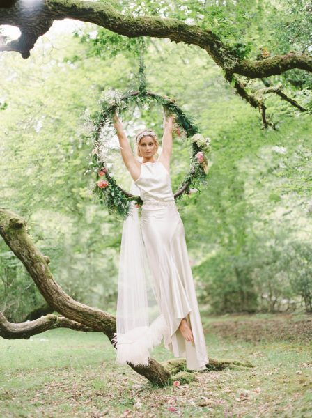 Dreamy Fine Art Fuji 400h image of a Bride hanging off floral foliage hoop in a forest scene wearing a Tara Bradley-Birt dress that is cascading down