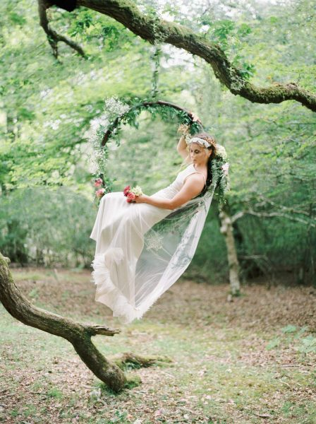 Dreamy Fine Art Fuji 400h image of a Bride sitting in a floral hoop holding dress out in a forest scene wearing a Tara Bradley-Birt dress with veil cascading down
