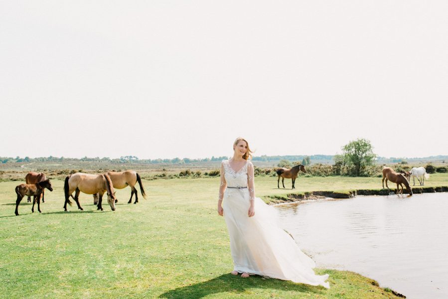 Dreamy Fine Art image of a Bride walking on heathland in Tara Bradley-Birt dress with New Forest ponies in the background