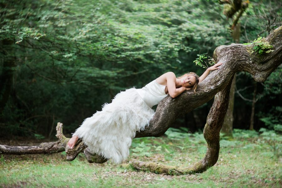 Dreamy Fine Art image of a Bride lying down on a tree trunk in an ostrich feather Tara Bradley-Birt dress
