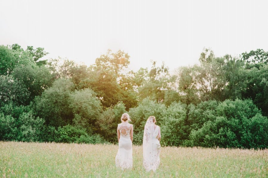 Fine Art fuji400h film full length portrait of two Brides walking away from camera into the distance in a dreamy bathed in golden light field for Tara Bradley-Birt bridal fashion shoot