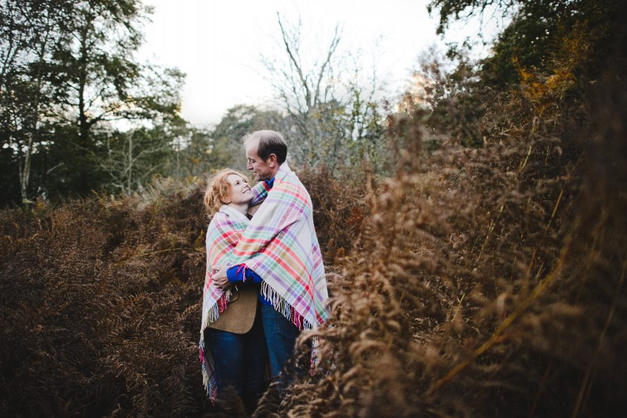 Autumn countryside Engagement LOVE shoot with couple snuggling under multicoloured rug blanket with a backdrop of golden bracken