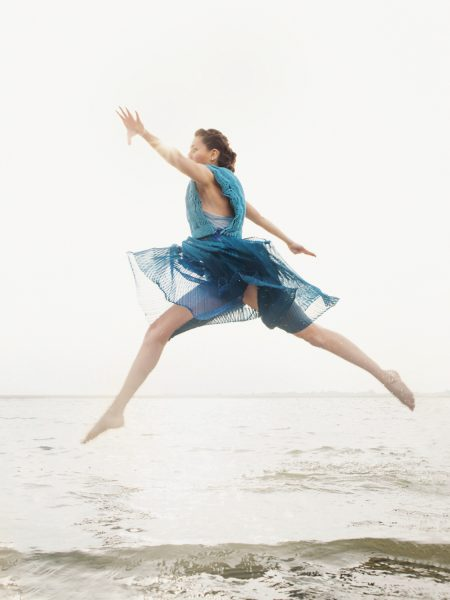 Fashion designer dancer beach shoot featuring brunette model leaping in air above sea out holding arms out wearing a transparent turquoise jersey knit dress on West WIttering West Sussex