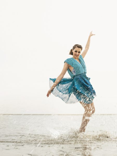 Fashion designer dancer beach shoot featuring brunette dramatically landing in sea stretching out arms in opposite directions in elegant balletic way wearing a transparent turquoise jersey knit dress on West WIttering West Sussex