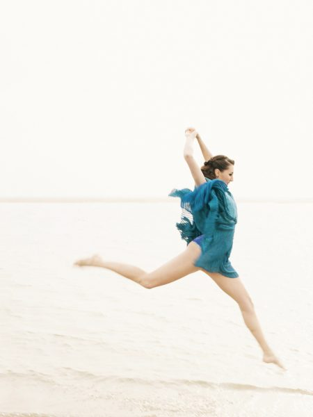 Fashion designer dancer beach shoot featuring brunette dramatically leaping high above swain an elegant balletic way wearing a transparent turquoise jersey knit dress on West WIttering West Sussex