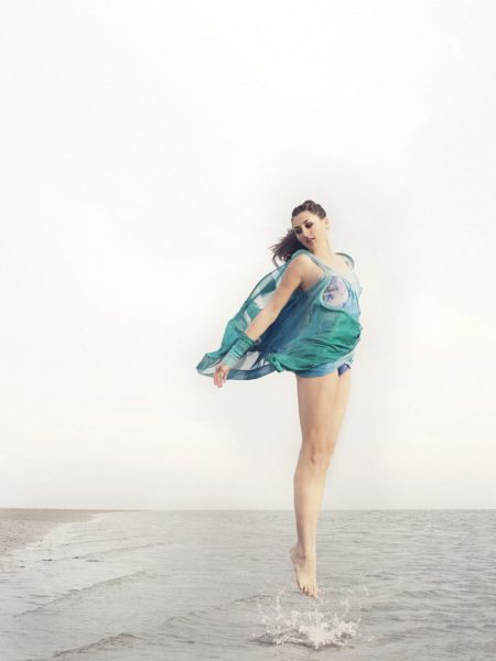 Fashion designer dancer beach shoot featuring brunette dramatically jumping up vertically out of sea in elegant balletic way wearing a transparent turquoise jersey knit dress on West WIttering West Sussex