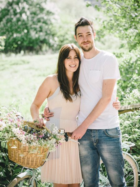 Pastel engagement shoot of portrait of engaged couple holding a vintage aqua bicycle with flowers in a basket in English West Sussex countryside