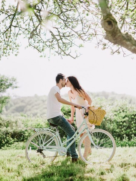 Pastel engagement shoot of Bride and Groom to be kissing under ancient apple trees with blossom perched on a vintage aqua bicycle with flowers in a basket in English West Sussex countryside