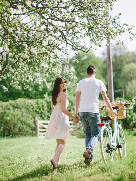 Pastel engagement shoot of portrait of engaged couple walking away from camera pushing a vintage aqua bicycle with flowers in the basket in English West Sussex countryside