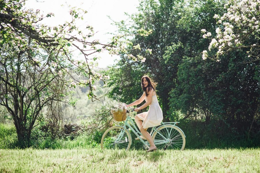 Pastel engagement shoot of Bride cycling in a blush coloured dress on a vintage aqua bicycle with flowers in a basket in English West Sussex countryside