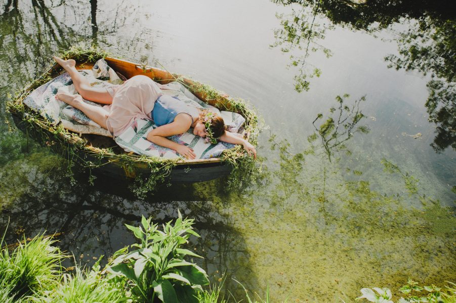 Pastel engagement shoot of a wide shot of water with Bride lying down relaxing on a rowing boat with beautiful water around. English West Sussex countryside