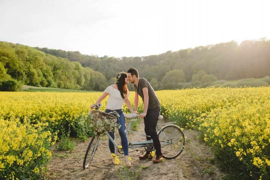 Pastel engagement shoot of a wide shot of Bride and Groom to be kissing whilst sitting on a blue tandem bike in a yellow field of rape seed. English West Sussex countryside