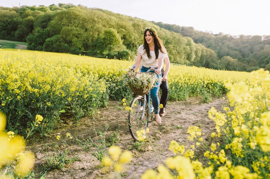 Pastel engagement shoot of Bride and Groom to be cycling a blue tandem bike in a yellow field of rape seed. English West Sussex countryside