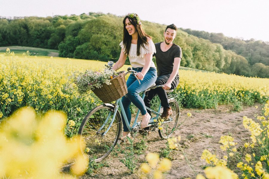 Pastel engagement shoot of Bride and Groom to be laughing while cycling a blue tandem bike in a yellow field of rape seed. English West Sussex countryside