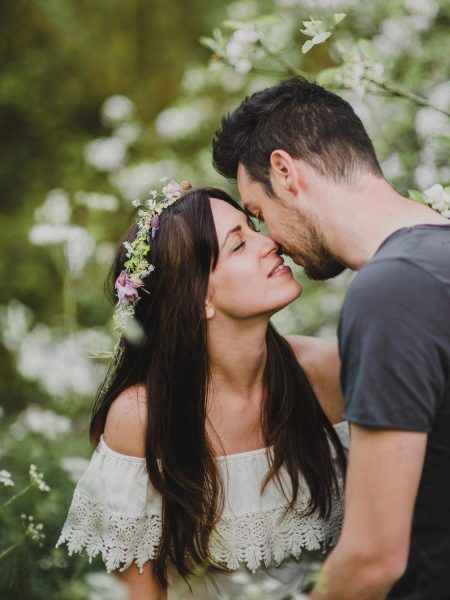 Pastel engagement shoot of Bride and Groom to be kissing under a tree of blossom English West Sussex countryside