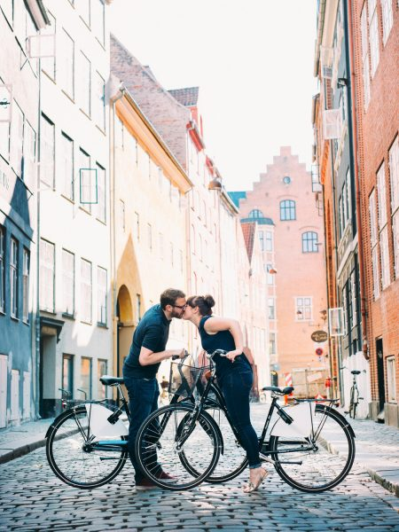 Love shoot Copenhagen featuring engagement couple kissing on bikes with old Copenhagen street with colourful buildings