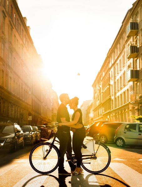 Love shoot Copenhagen featuring engagement couple kissing on bikes in middle of an old Copenhagen street sunlit orange as the sun sets