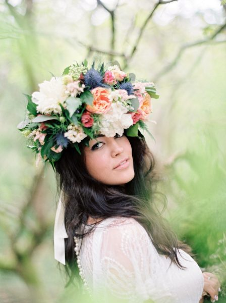 Fine Art Boho forest shoot with model looking at camera in a wedding dress and rustic floral crown headdress in pink, orange coral antique roses cream peony and lilac