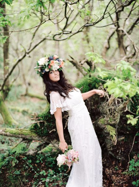 Fine Art Boho forest shoot with model looking at camera in a wedding dress and rustic floral crown headdress in pink, orange coral antique roses cream peony and lilac holding onto a fallen tree trunk with moss