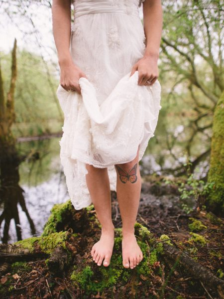 Fine Art Boho forest shoot with model close up of wedding dress below shoulders as model reveals butterfly tattoo as she stands on a mossy rock with a dramatic bog behind her