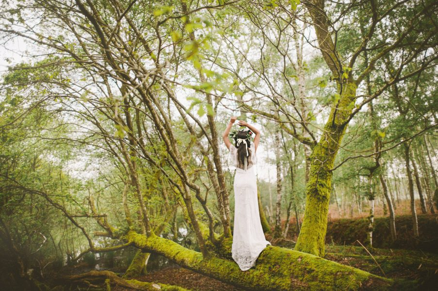 Fine Art Boho forest shoot with back view of model in wedding dress with scalloped edge sheer embellished cape lifting arms above head standing on mossy fallen tree
