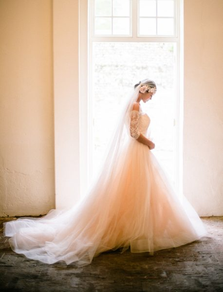Fine Art Bignor Park shoot featuring a bride standing in a doorway in a Blush tulle dreamy JLM, Tara Keely wedding dress