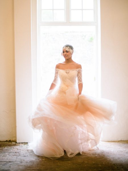 Fine Art Bignor Park shoot featuring a Bride twirling around in a doorway wearing a Blush tulle dreamy JLM, Tara Keely wedding dress